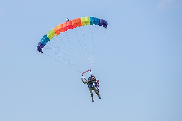 a sky diver parachutes onto the field at The Diamond before the game on July 10.