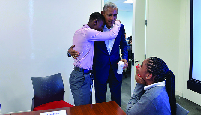 President Obama hugs Aaron Park, a Youth Jobs Corps intern, during his surprise visit to the Obama Foundation Headquarters where he met with 13 students who, like Park, are also participating in the Youth Jobs Corps program. Photo Credit: The Obama Foundation