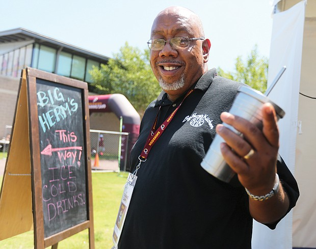 Herman Baskerville, owner of Big Herm's Kitchen, shows the sign that points hungry and thirsty fans to his food concession at the Washington NFL team training camp in Richmond, where for the third consecutive year, he is the sole African-American vendor.