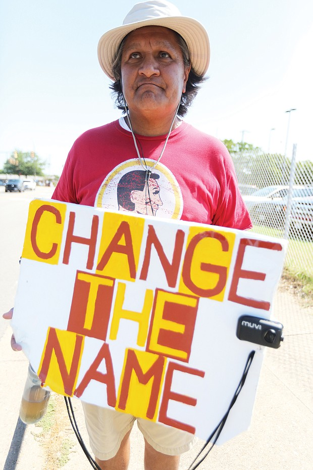 "Stephen Rivera of Richmond carries his message on a sign outside the team's training camp on West Leigh Street. He has picketed against the team's racist name each year since the team began practicing in Richmond in 2013. He has no suggestion for a new name but says anything is fine ""as long as it's not something that denigrates native people or any of us."" A U.S. Supreme Court decision in June regarding ""immoral"" or ""scandalous"" trademarks may bolster the team's legal efforts to keep its offensive, trademarked name."