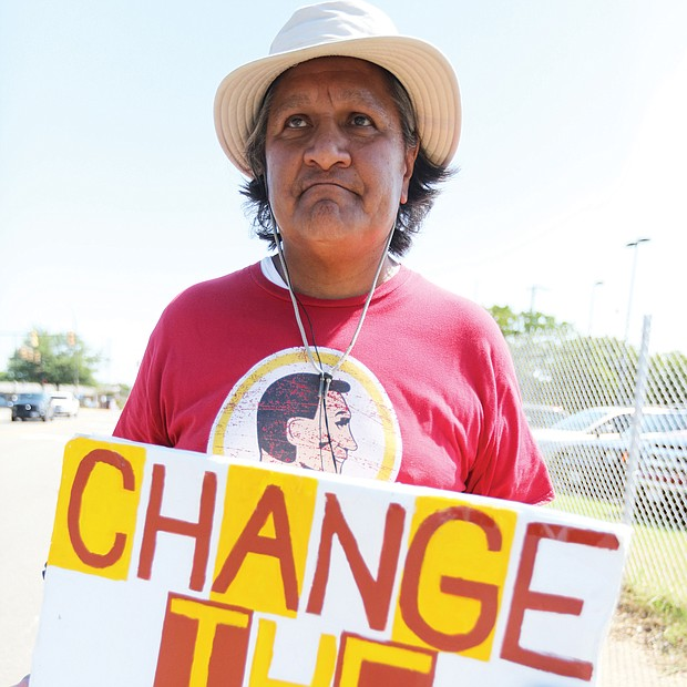 """Stephen Rivera of Richmond carries his message on a sign outside the team's training camp on West Leigh Street. He has picketed against the team's racist name each year since the team began practicing in Richmond in 2013. He has no suggestion for a new name but says anything is fine """"as long as it's not something that denigrates native people or any of us."""" A U.S. Supreme Court decision in June regarding """"immoral"""" or """"scandalous"""" trademarks may bolster the team's legal efforts to keep its offensive, trademarked name."""