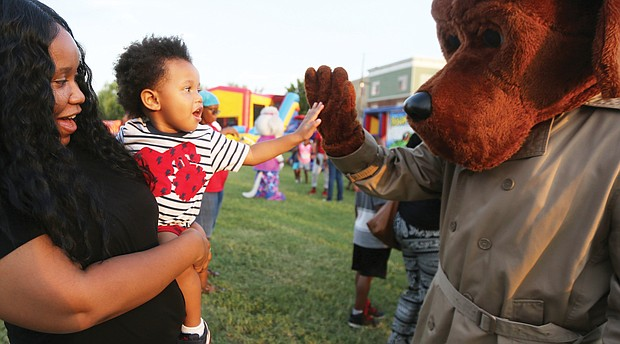 Jeremiah Jackson, 2, gives a high five to McGruff the Crime Dog from the arms of his mom, Kahdijah Overstreet, during the National Night Out event hosted Tuesday evening by Sixth Mount Zion Baptist Church in Jackson Ward.