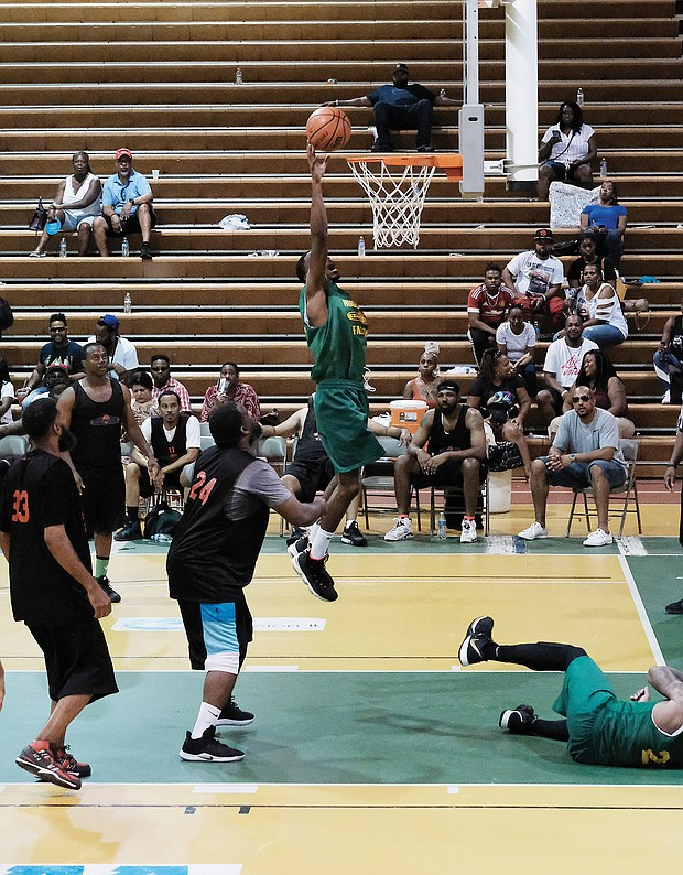 Huguenot High School alumnus Olajuwan Johnson goes up to the rim to score against Thomas Jefferson High School alumni during the championship game in last Saturday's Richmond Public Schools Alumni Basketball Showdown at the Arthur Ashe Jr. Athletic Center. Mr. Johnson was named tournament MVP.