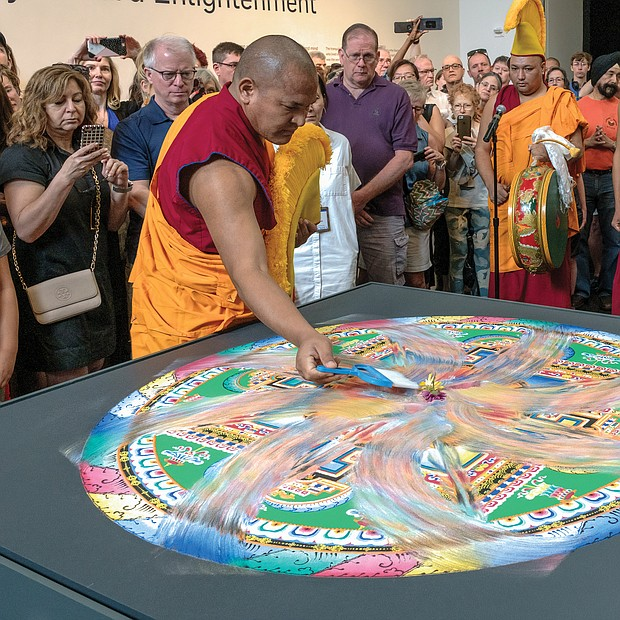 """Sweeping away the mandala Tibetan Buddhist monks from the Drepung Loseling Monastery in Southern India dismantle a sand mandala they constructed in early May at the Virginia Museum of Fine Arts in conjunction with the opening of the museum's exhibit, """"Awaken: A Tibetan Buddhist Journey Toward Enlightenment."""" With the exhibit's closing this week, the monks dismantled the mandala in a ceremony last Saturday, sweeping up the sand to symbolize the impermanence of all that exists. (photo by Ava Reaves)"""