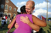 Chiquita Compton gives Richmond Police Chief Will Smith a big hug during his visit to the National Night Out festivities at Jackson Ward's Sixth Mount Zion Baptist Church on Tuesday.