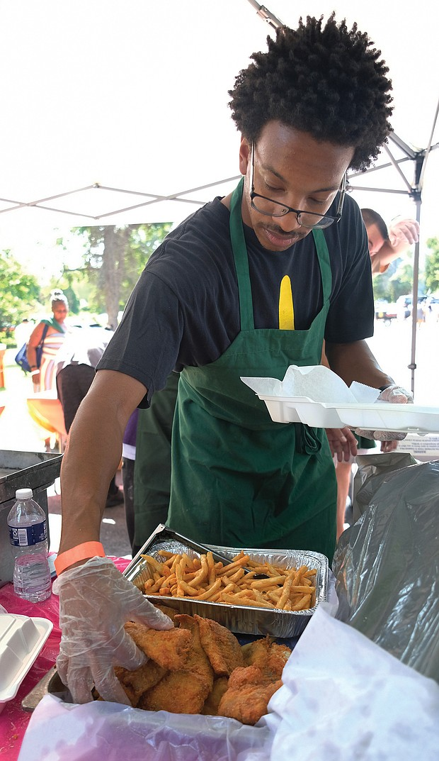 Marquis Smith serves up fish and fries at the 11th Annual St. Elizabeth Catholic Church Jazz & Food Festival. (Sandra Sellars/Richmond Free Press)