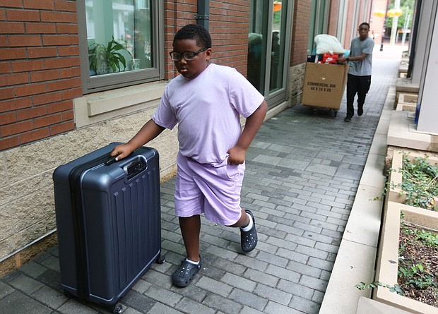 Cityscape: Slices of life and scenes in Richmond/Noah McKay, 11, of Charlotte, N.C. and Desmond Baah, 17, provided the muscle to move a big suitcase and a large box filled with shoes, clothes and other essentials for student life. The student move-in at VCU mirrored similar activity this month at Virginia Union University and the University of Richmond as new and continuing students prepared for the start of classes. (Regina H. Boone/Richmond Free Press)