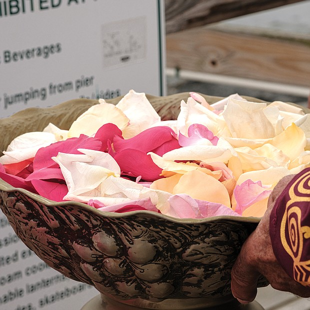 Calvin Pearson, founder of Project 1619, holds a bowl of rose petals in preparation for a ceremony in which people dropped the petals in the water off the pier at Fort Monroe in honor and remembrance of the millions of Africans brought to these shores during the trans-Atlantic slave trade. (photo by Ava Reaves)