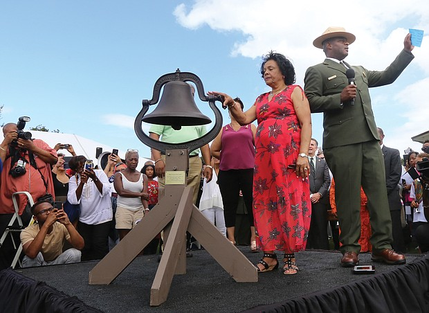 Ora McCoy, 76, of Appomattox, and Terry E. Brown, superintendent of Fort Monroe National Monument, launch the nationwide bell-ringing ceremony at 3 p.m. Sunday at Fort Monroe as part of the ceremony. Bells at national parks, churches and other places across the country rang for four minutes — one minute for each century — in honor of the first Africans in English North America 400 years ago. The bell belonged to Ms. McCoy's family. (Regina H. Boone/Richmond Free Press)
