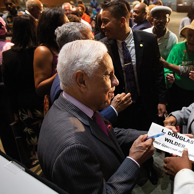 """Former Virginia Gov. L. Douglas Wilder, a grandson of slaves and the first African-American elected governor in the nation, autographs a placard for a guest at the """"African-American Political Pioneers"""" luncheon Friday at the Hampton Roads Convention Center. (photo by Brian Palmer)"""
