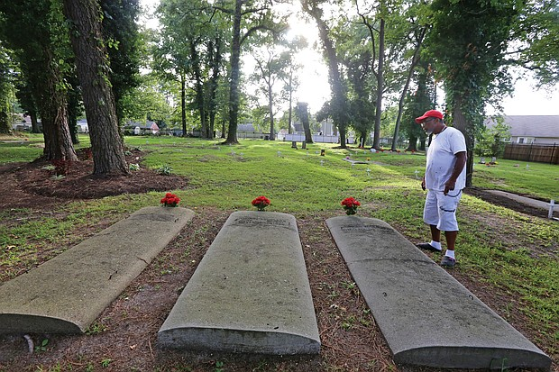Tracy Richardson of Hampton looks at some of the marked gravesites at the Tucker Family Cemetery nestled in a residential area at 1 Sharon Court in Hampton. The cemetery holds the descendants of William Tucker, the first African-American born in the English colony of Virginia in 1624. According to records, William Tucker was the child of Anthony and Isabella, two of the first Africans brought to Virginia in 1619. (Regina H. Boone/Richmond Free Press)