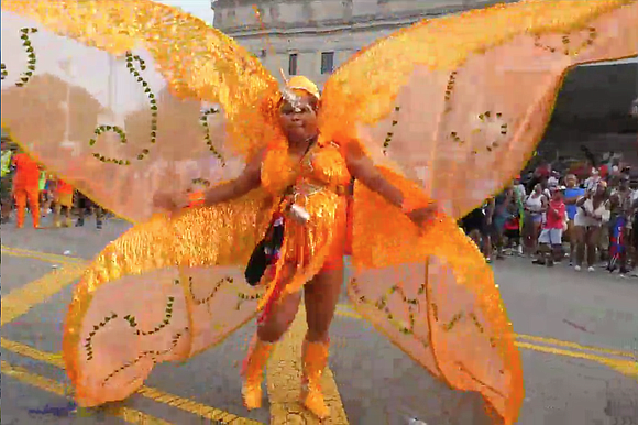 Steel bands and revelers sporting elaborate feathered costumes, Caribbean flags and some rain ponchos marched and danced Monday in a ...