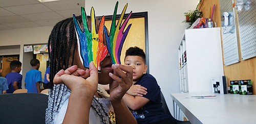 A Blazers Boys & Girls Club member in northeast Portland shows off her 'All about You' handprint, created during the club's first community art project in the new Michaels MakerSpace, part of a new partnership with Michaels, the national chain of arts and crafts stores.