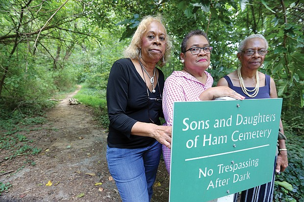 From left, Diane W. Jones and her sister, Carolyn W. Moten, and cousin Linda T. Nash stand in front of the sign for the overgrown cemetery in Henrico County where their relatives are buried and which they are working to restore.