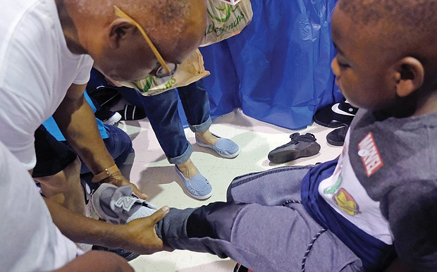 Larry Christian helps his grandson, Makhi Peterson, 5, try on new sneakers at the event.