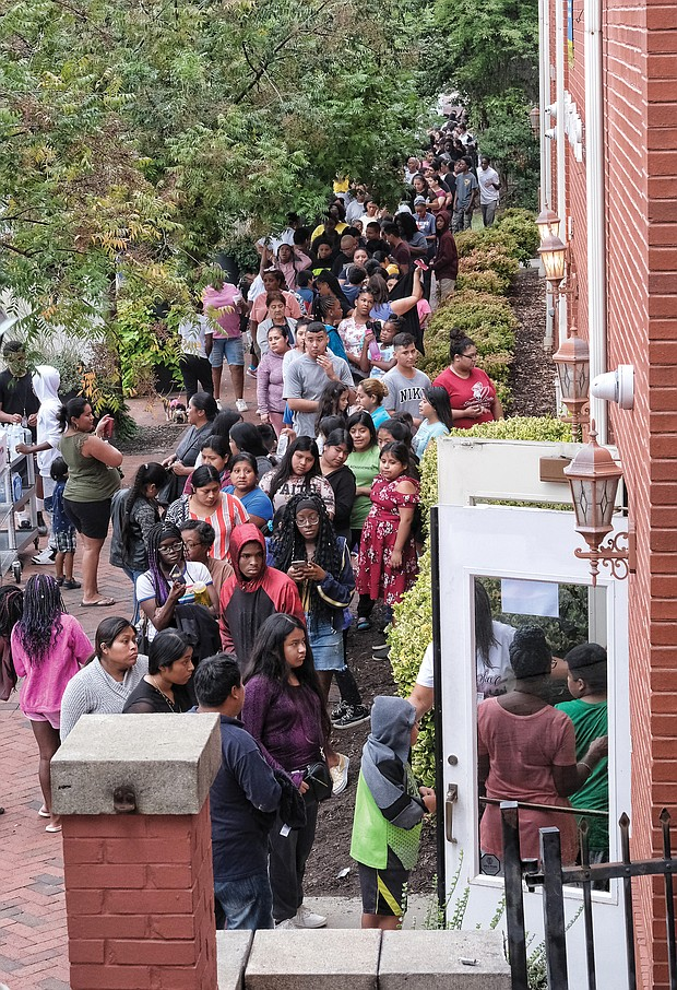 Hundreds of people line up outside the doors of Third Street Bethel A.M.E. Church in Jackson Ward on Monday for the 14th Annual Labor Day New Shoes for Back to School program. Students in kindergarten through high school could pick out a pair of new shoes to start the school year.