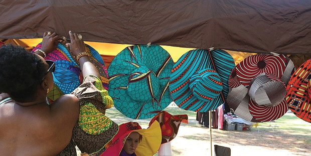 Georgia Bates of Henrico, above, adjusts the Ankara hats designed by her sister, Massa Watson, at a booth at the 2019 AfroFest RVA last Saturday. The event, sponsored by the city Department of Parks, Recreation and Community Facilities, was held at Pine Camp Cultural Arts and Community Center in North Side. It highlighted the culture, food, music and fashions of people from African nations living within the Richmond community, along with a championship soccer match between teams from Ghana and Sudan.
