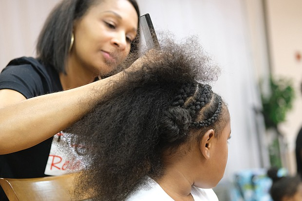 Coordinator of the event, Monique Brown, braids the hair of Nyla-Marie Outlaw, 6.