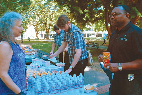 Community volunteer Lisa Klein visits with Ray Turner Jr. of Portland 5 Center for the Arts as she hands out free hot dogs, chips and water at Holladay Park during a special event to celebrate a successful effort to reduce crime in the park.