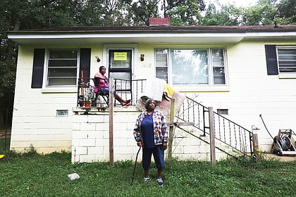 The Lewis sisters in front of the condemned house on Flynn Road in South Side that they no longer are allowed to live in.
