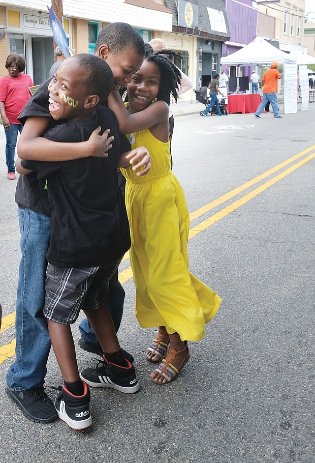 We won! The Aryee siblings — from left, Caleb, 9; Othneil, 12; and Zari, 9 — celebrate after learning they won a bicycle in a raffle at the 6th Annual Brookland Park Community Celebration last Saturday in North Side. The event, sponsored by the Historic Brookland Park Collective, featured food, music and fellowship along West Brookland Park Boulevard that was closed to traffic. The youngsters used the no traffic zone to happily and freely road test their new bike. (Sandra Sellars/Richmond Free Press)