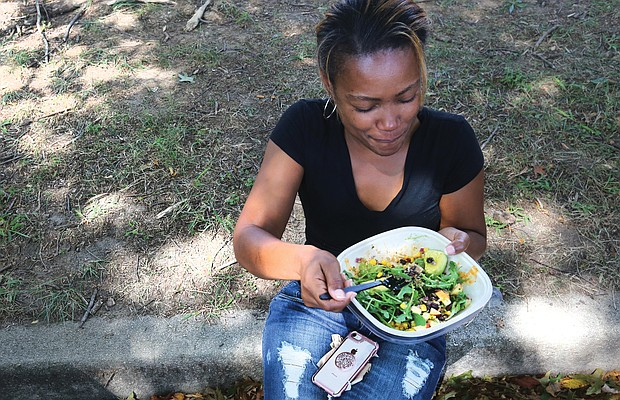 Vegan for the soul/Aranda Goodwin of Virginia Beach sits in the shade to enjoy a raw vegan salad from Goatocado, a restaurant in The Fan that had a booth at the event. In addition to food, the block party featured cooking demonstrations, speakers, music and dancing. (Regina H. Boone/Richmond Free Press)