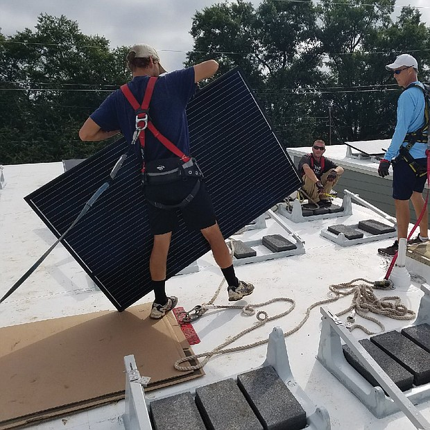 Installers put a solar panel in place on the roof of a new home in the 1200 block of West Leigh Street.