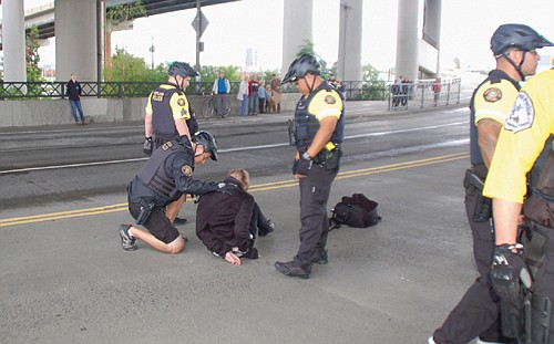 """There were three arrests during Friday's climate strike march from downtown Portland to the east side near OMSI, including this one of a man who only identified himself as """"Jake,"""" accused of spray painting graffiti on the Hawthorne Bridge. The two other arrests of young people, however, brought complaints of police brutality from the Urban League of Portland and City Commissioner Jo Ann Hardesty."""