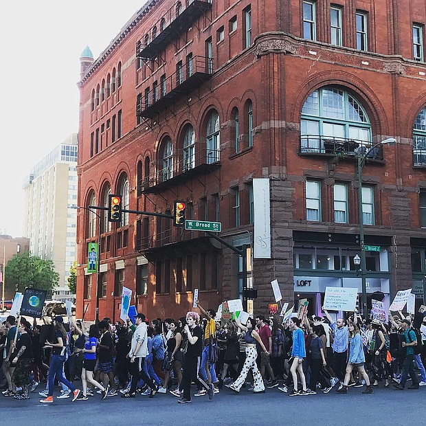 Hundreds of marchers walk along Broad Street in Downtown during an early evening rally and march last Friday from Monroe Park to City Hall as part of the Global Climate Strike.