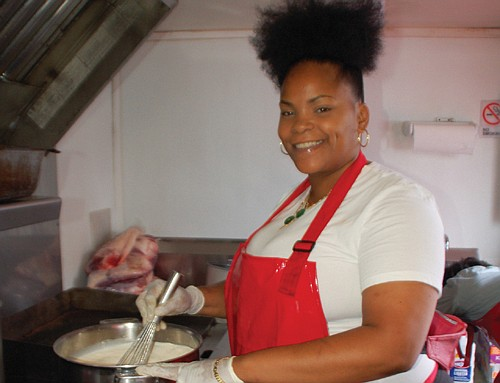 Kiauna Nelson, owner of Kee's #Loaded Kitchen, stirs a big pot of cheese sauce for her signature mac and cheese. The food cart is a Portland destination for good eats, known for its mouthwatering soul food and servings big enough for leftovers or sharing with friends.