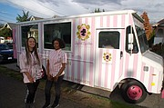 """Rita Calloway (right), the owner of """"Styled by Her Beautique,"""" a new mobile beauty salon that comes to you for hair care and other services, outside her beauty shop on wheels with a recent customer, Madalyn Davis (left)."""