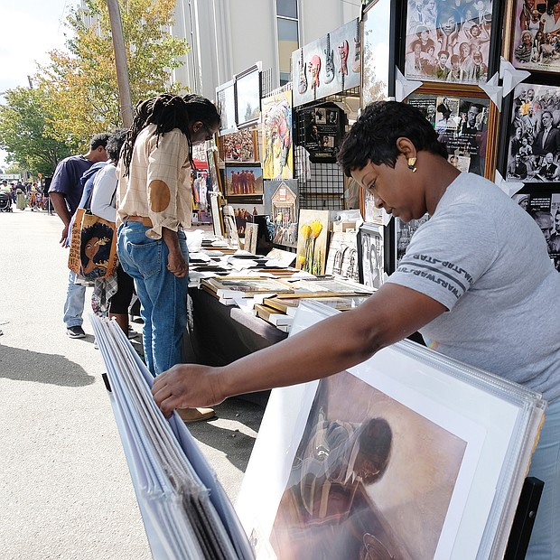 Caroline Johnson peruses art for sale by one of the many vendors and merchants at the 31st Annual 2nd Street Festival. (Sandra Sellars/Richmond Free Press)