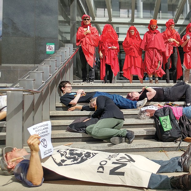 "Members of Extinction Rebellion Richmond stage a silent die-in on the steps of City Hall around noon on Monday as members calling themselves the ""Red Rebel Brigade"" look on. The 11-minute action, designed to call attention to the need for action to abate climate change, came after the group delivered a Declaration of the Global Climate Emergency to the office of Mayor Levar M. Stoney, urging him and other officials to declare a climate state of emergency in the city. The group has demonstrated weekly