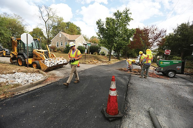 The Fulton neighborhood in the East End is one of the first to get new paving as part of a $15 million program City Hall is undertaking during the current 2019-20 budget year. While one lane on Carlisle Avenue is complete, a city crew on Monday repairs the second lane at the intersection of Carlisle Avenue and Malone Street before repaving. (Regina H. Boone/Richmond Free Press)