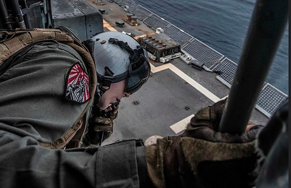 SOUTH CHINA SEA (October 10, 2019) Naval Aircrewman (Helicopter) 3rd Class Cristopher Woolsey, from Houston, assists in landing an MH-60R ...