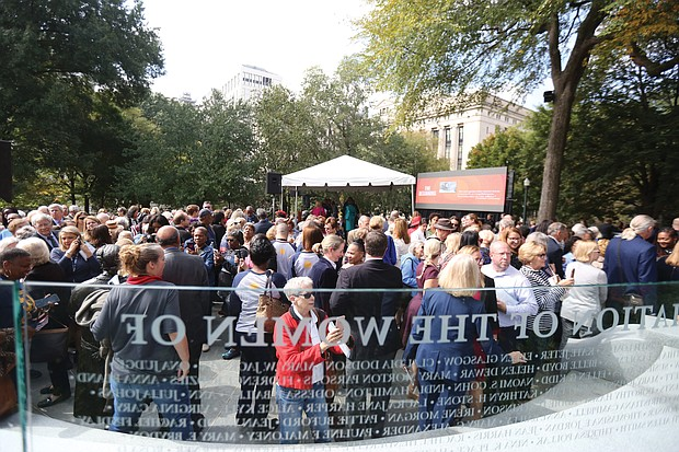 Throngs of people walk around the Virginia Women's Monument in Capitol Square following Monday's dedication ceremony. In addition to the bronze statues, the monument has a curved glass Wall of Honor etched with the names of 230 outstanding Virginia women who made contributions to the state and nation during the last 400 years.