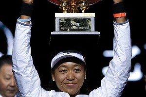 Naomi Osaka lifts high her winner's trophy after defeating Ashleigh Barty of Australia in the women's final at the China Open tennis tournament in Beijing on Oct. 6.