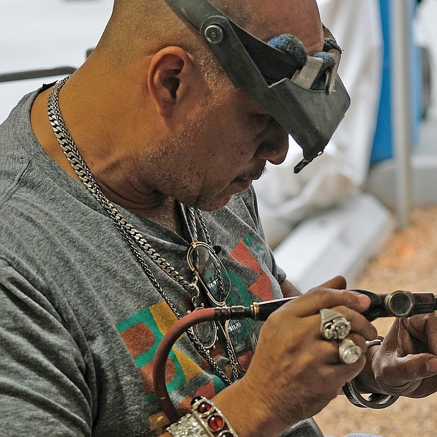 Lots of music, lots of folk/Richmond's Downtown riverfront came alive with people and music last weekend as thousands of people turned out for the Richmond Folk Festival. Emanuel Carona of Third Generation Jewelers in Milwaukee, one of scores of artisans and artists displaying their work during the festival, carefully crafts a bracelet. (Sandra Sellars/Richmond Free Press)