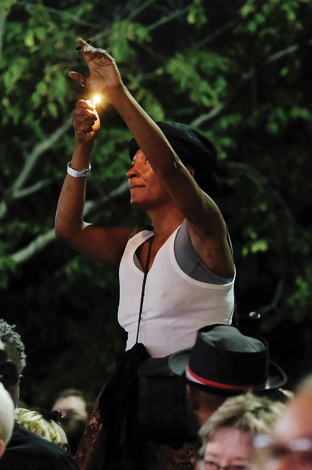 Lots of music/lots of folk/Richmond's Downtown riverfront came alive with people and music last weekend as thousands of people turned out for the Richmond Folk Festival. One audience member shows her appreciation by shining a light. (Sandra Sellars/Richmond Free Press)