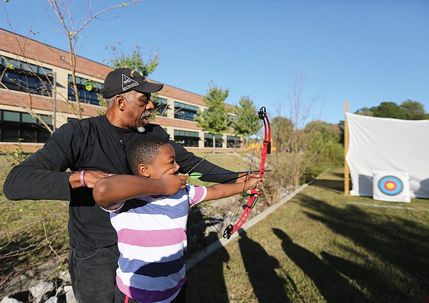 Aiming for the target: Josh Morris, a fourth-grader at Broad Rock Elementary School in South Side, learns how to set his arrow in a bow to accurately hit the target during an after-school program last Friday with recreation specialist Wyatt Kingston of the Richmond Department of Parks, Recreation and Community Facilities. Mr. Kingston, who beame certified to teach archery more than a decade ago, gives group and individual instruction to youngsters. He was working last week with students at the Broad Rock Community Center, and will rotate among the various recreation centers in Richmond. His ultimate goal, he said, is to build the skills of youngsters to the point that they can compete in local and state competitions.