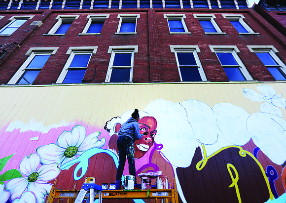 Artist Austin Miles of Petersburg puts the finishing touches last week on this new mural that now decorates Max Market, ...