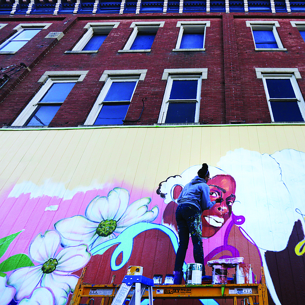 """Cityscape: Slices of life and scenes in Richmond-Artist Austin Miles of Petersburg puts the finishing touches last week on this new mural that now decorates Max Market, 1125 Hull St. She is contributing the fine details to the mural that began with a community paint day Oct. 5. The mural is the first of a planned series titled """"Brown Girl Narratives"""" that Kristal Brown, founder and leader of Black Women Cache LLC, is spearheading. This and other murals will help fulfill the goal of the organization, Ms. Brown said, which is """"to highlight the lived experiences of black women through media and visual arts."""" Next year, the Virginia Commonwealth University doctoral student plans to release a coffee table book focusing on black women and hold other events. (Regina H. Boone/Richmond Free Press)"""