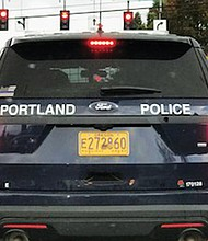 "A posting on Twitter shows a Portland Police vehicle window with the political ""Blue Lives Matter"" flag attached to the bottom left corner."