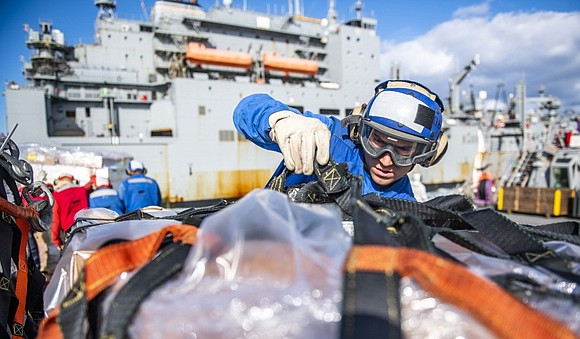 Boatswain's Mate 3rd Class Avery Gonzalez, from Houston, removes a cargo net from a pallet on the flight deck of ...