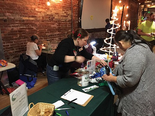 Terra Heilman helps a resident pick holiday fabric for reusable gift wrapping bags as coordinator for The Repair Clark County reuse and recycle program which helps residence reduce their waste.