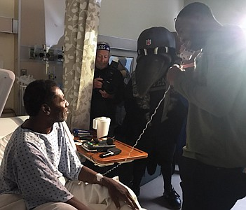 Former Ravens wide receiver Torrey Smith speaks to the wife  of Lewis Walden Jr. by phone amidst the glare of media lights. Smith surprised Walden during a visit to the Baltimore VA Medical Center as a part of a salute Veterans on November 14, 2019