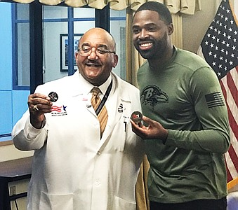 ( Left):  VA Maryland Health Care System Director Dr. Adam Robinson, Jr. and former Ravens wide receiver Torrey Smith show off commemorative pins during a visit to the  Baltimore VA Medical Center as a part of a salute Veterans November 14, 2019.