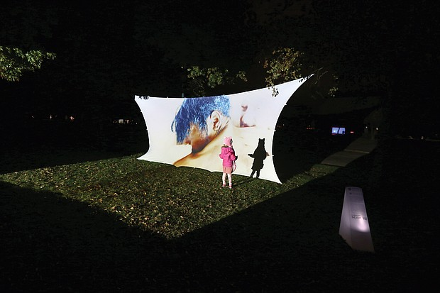 """A youngster is intrigued by her shadow on an art installation at Chimborazo Park last Friday and Saturday as part of 1708 Gallery's InLight 2019, an annual exhibition of light-based art and performances. About 20 pieces were at the free, two-day, outdoor exhibit in Church Hill focused on the social and geographic history of the park, which served as one of the largest Confederate military hospitals during the Civil War and afterward a community for formerly enslaved people. The installation the youngster enjoyed is """"Pieces of Us"""" by Allicette Torres."""