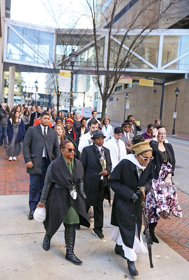 Queen Nzinga of Richmond leads a procession of Virginia Commonwealth University officials, students and others as they welcomed and paid their respects as the remains were returned to the VCU medical campus. Elegba Folklore Society members poured libations honoring those whose remains were returned during a ceremony in the courtyard of the Hermes A. Kontos Medical Sciences Building at 12th and Marshall streets. The remains were found in a well during the 1994 construction of the building.