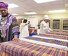 Richmond Delegate Delores L. McQuinn, a minister and chair of the Richmond Slave Trail Commission, prayerfully puts her hand on the Kente cloth covering one of 17 boxes of human remains found in 1994 in a well on Virginia Commonwealth University's medical campus. The remains, which were returned to Richmond during a ceremony on Monday, will be stored by the state Department of Historic Resources while planning for an appropriate burial and memorial continues.